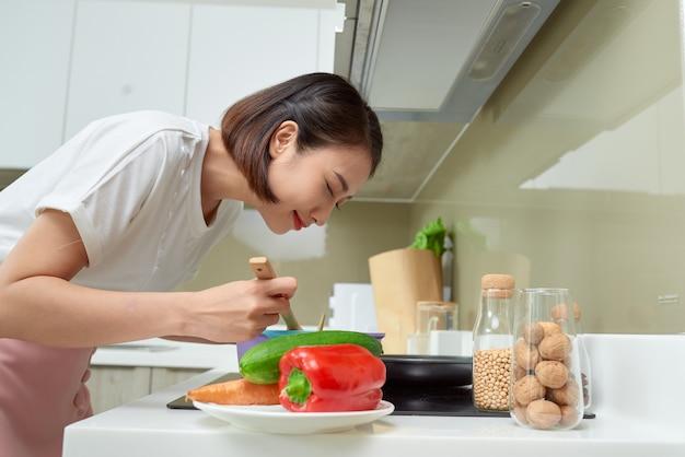 부엌에서 요리하는 젊은 여자. 건강 식품. 다이어트 개념입니다. 건강한 생활. 집에서 요리하기. 음식을 준비하다