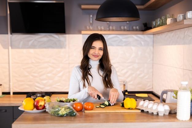 台所で料理をしている若い女性。健康食品。ダイエットの概念。健康的な生活様式。家庭での料理。食べ物を用意します。
