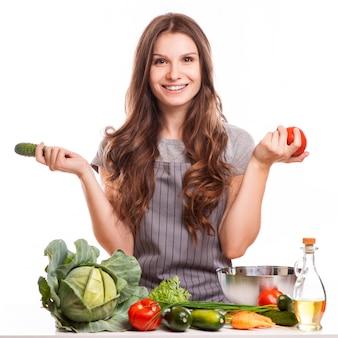 Молодая женщина приготовления пищи на кухне. здоровая пища