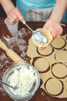 Девушка готовит на кухне, подготавливает тесто для выпечки, добавляет творожную начинку в пирог