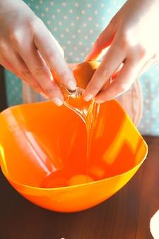 부엌에서 요리하는 젊은 여성이 제빵을 위해 반죽을 준비하고 계란을 그릇에 나눕니다.