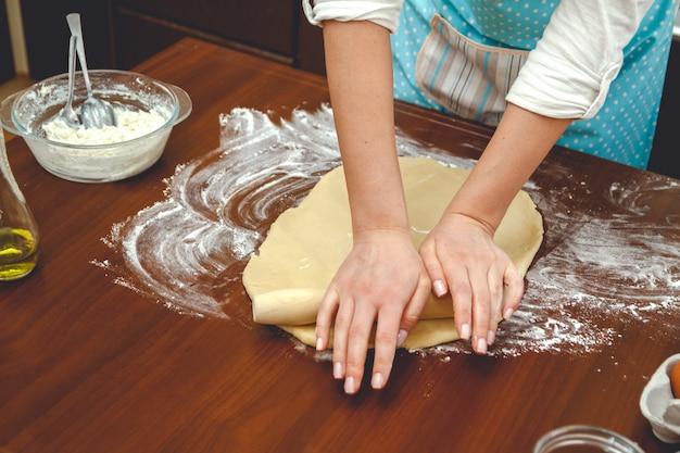 キッチンで調理する若い女性は、テーブルで焼くために麺棒で生地を転がします