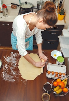 부엌에서 요리하는 젊은 여자, 테이블에 베이킹을위한 롤링 핀으로 반죽을 롤