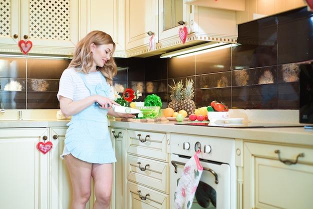 台所で料理をしている若い女性。