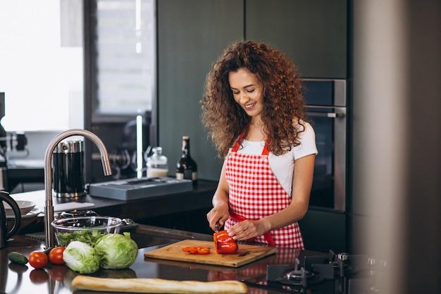 Giovane donna che cucina alla cucina