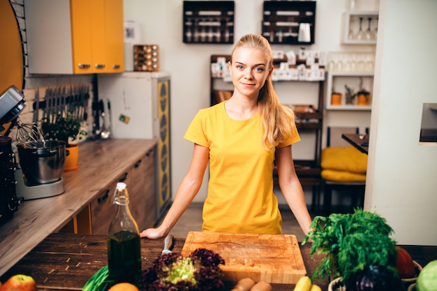 若い女性が健康食品、キッチンで調理。ベジタリアンダイエット、新鮮な野菜や果物