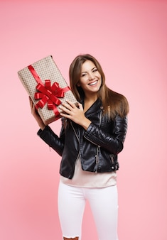 Young woman in cool outfit holding birthday present looking straight