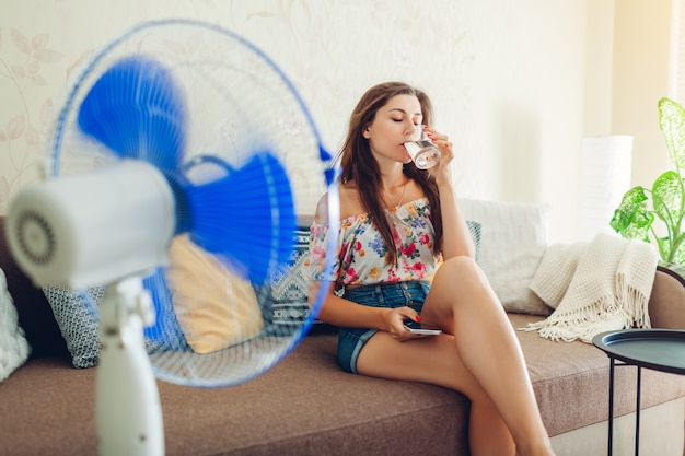 Young woman cooling down by ventilator at home while drinking water and hanging in phone.