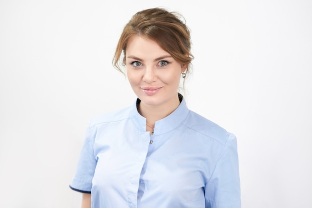白い背景の上の若い女性の美容師。プロセッションの美容師の肖像画