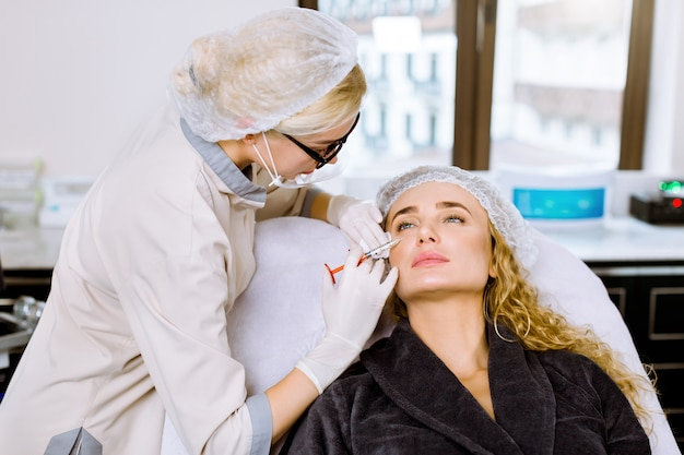 Young woman cosmetologist performs the botox procedure in the clinic to beautiful blond woman. cosmetology.