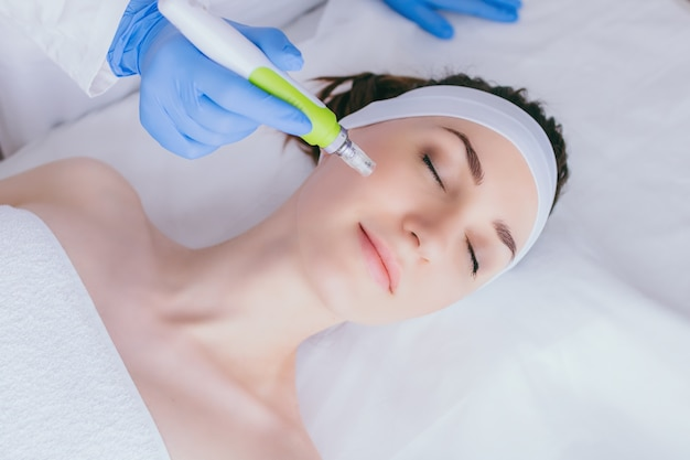 A young woman in the cosmetologists office receives fractional mesotherapy for her face