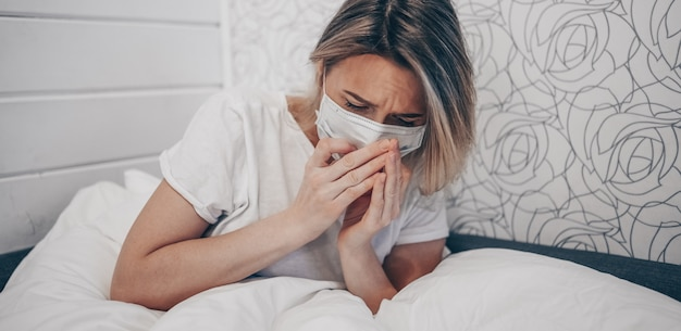 Young woman coughing in arms sick of coronavirus viral infection spreading corona virus covering mouth and nose. painful cough ill patient lying in bed at home quarantine isolation. first symptoms