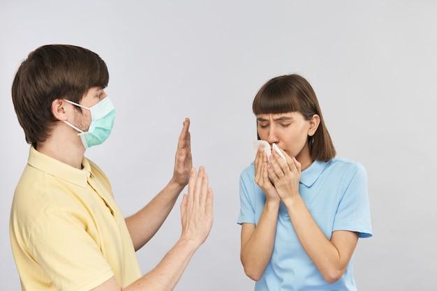 ナプキンに咳をする若い女性と彼女から離れたレスピレーターマスクシューイングの男性、コロウイルスの間距離を保つ