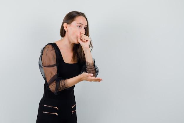 Молодая женщина кашляет во время разговора с кем-то в черной блузке и выглядит больной. передний план. место для текста