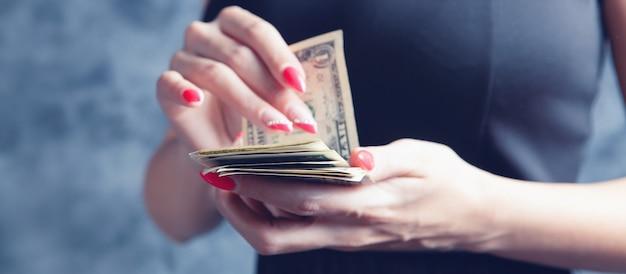회색 배경에 돈을 세는 젊은 여자