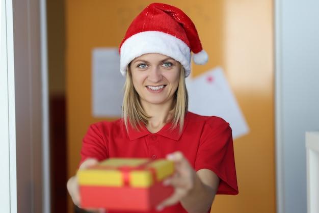 Молодая женщина-курьер в шляпе санта-клауса держит коробку с подарком в руках