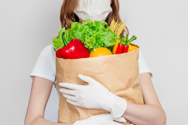 Young woman courier volunteer wearing a medical mask holds a paper bag with products, vegetables, chili, herbs isolated over white, gray space,  food delivery concept