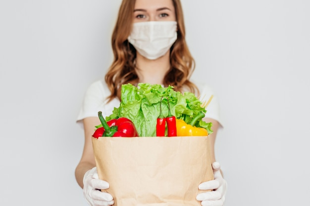 Young woman courier volunteer wearing a medical mask holds a paper bag with vegetables isolated , safe food delivery