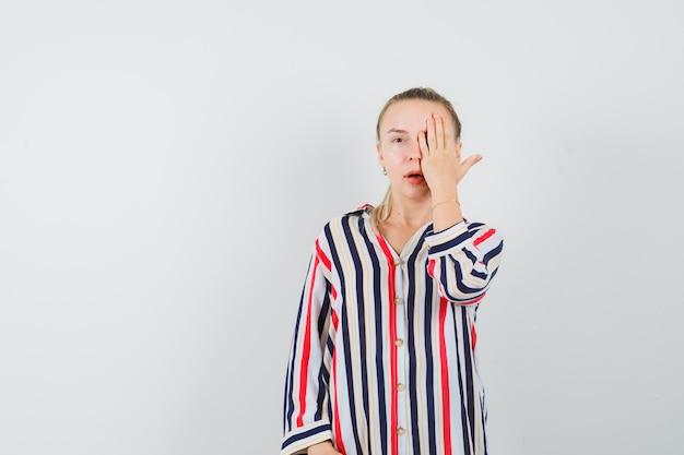 Молодая женщина закрыла один глаз рукой в полосатой блузке и выглядела красивой