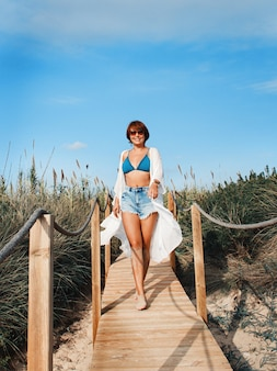 Young woman in cover up and jeans shorts walking between dunes.  travel and vacations concept.