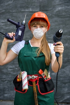 Young woman in coverall with drill machines in hands posing with tool belt