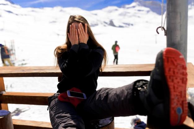 Молодая женщина закрыла лицо руками и уселась зимой у гор