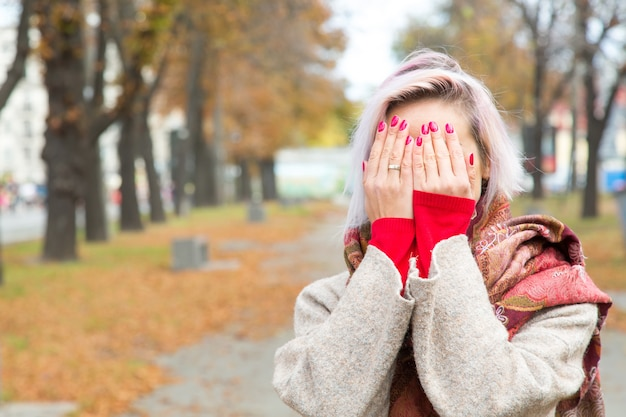 Young woman covered her face with her hands