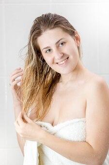 Молодая женщина, покрытая банным полотенцем после душа