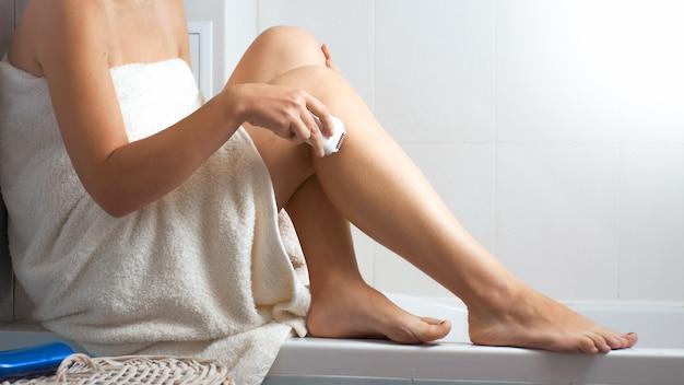 タオルで覆われた若い女性が脱毛をし、バスルームの脱毛器で脚から脱毛します。
