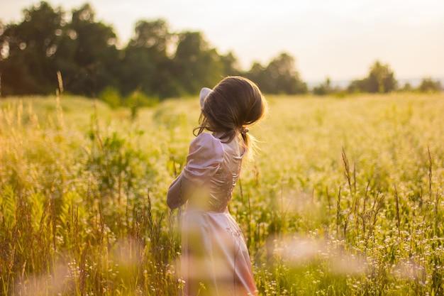 젊은 여자는 따뜻한 여름 저녁에 긴 분홍색 드레스에 야생화 필드에 서있는 긴 머리로 덮여 있습니다.