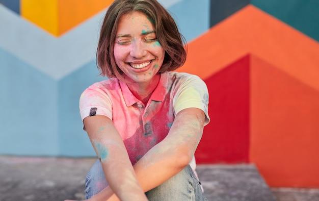 Молодая женщина покрыта краской смеется
