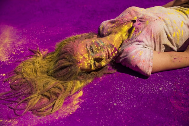 Young woman covered with powder lying on purple holi color