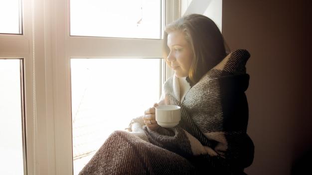 窓際に座ってお茶を飲む格子縞の若い女性covereng
