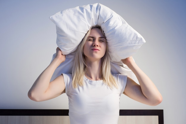 Young woman covering ears with pillow because of noise. - image