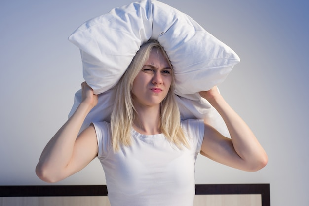 Young woman covering ears with pillow because of noise.