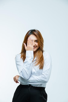 Young woman covering eye with hand and looking happy