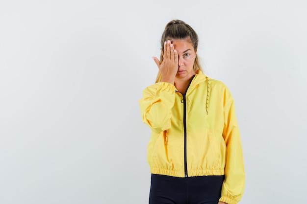 Giovane donna che copre gli occhi con la mano in bomber giallo e pantaloni neri e sembra seria