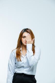 手で目を覆う若い女性