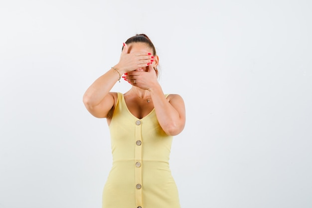 Young woman covering eyes and mouth with hands in yellow dress and looking scared , front view.