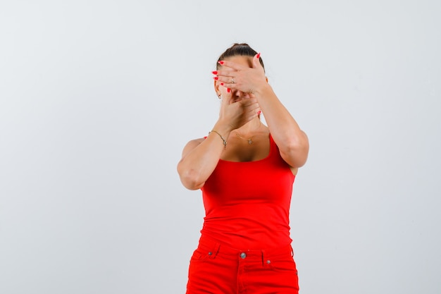 Young woman covering eyes and mouth with palms in red tank top, pants and looking upset , front view.