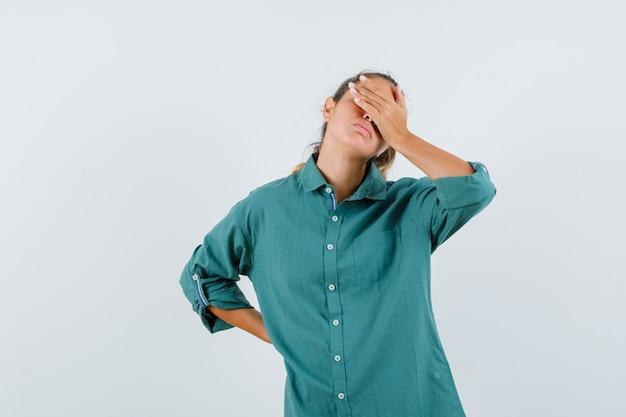 Giovane donna che copre gli occhi con la mano in camicetta verde e sembra stanca
