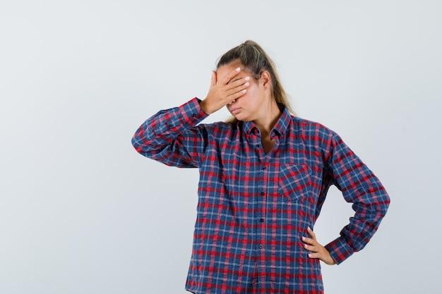 Giovane donna che copre gli occhi con la mano mentre si tiene una mano sulla vita in camicia a quadri e sembra infastidita