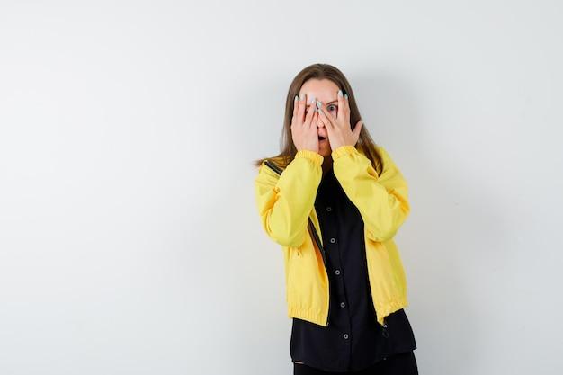 Молодая женщина, закрывая глаза руками и глядя сквозь пальцы