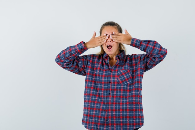 Young woman covering eyes with hands and yawning in checked shirt and looking sleepy