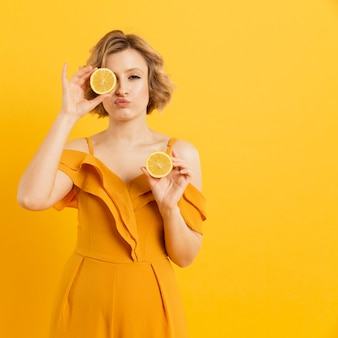 Young woman covering eyes with lemon slices