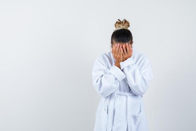Молодая женщина закрыла лицо рукой в халате и выглядела забывчивой