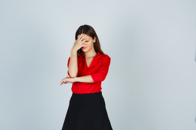 Giovane donna che copre il viso con la mano in camicetta rossa, gonna nera e sembra infastidita