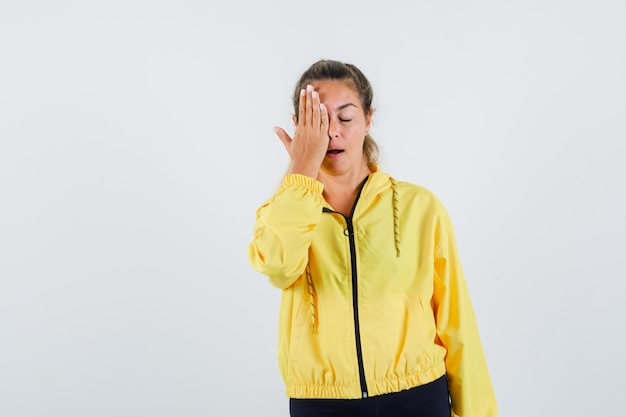 Young woman covering face with hand in yellow raincoat and looking calm
