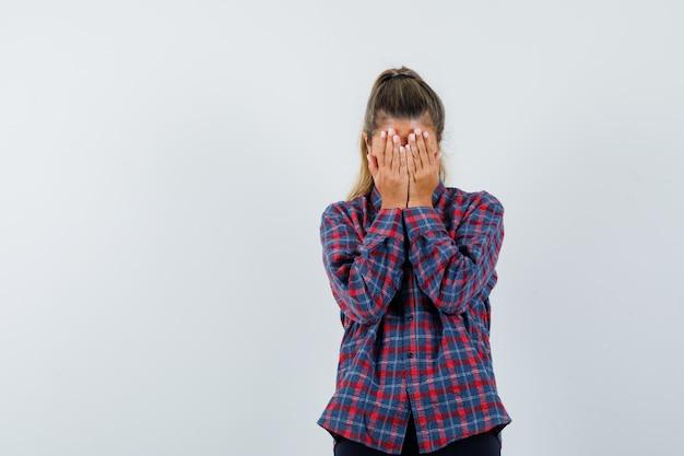 チェックシャツを着て手で顔を覆い、疲れている若い女性 無料写真