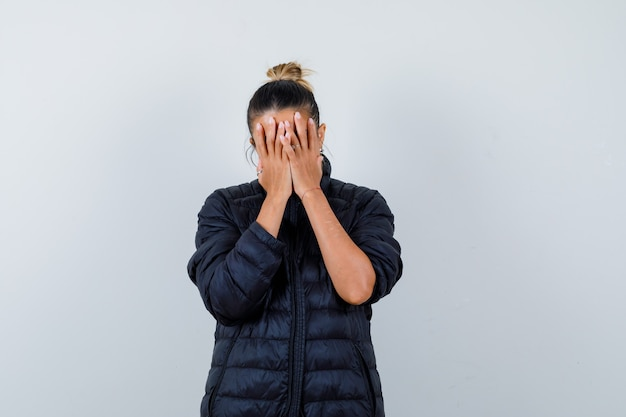 ダウンジャケットを着て手で顔を覆い、落ち込んでいる若い女性。正面図。